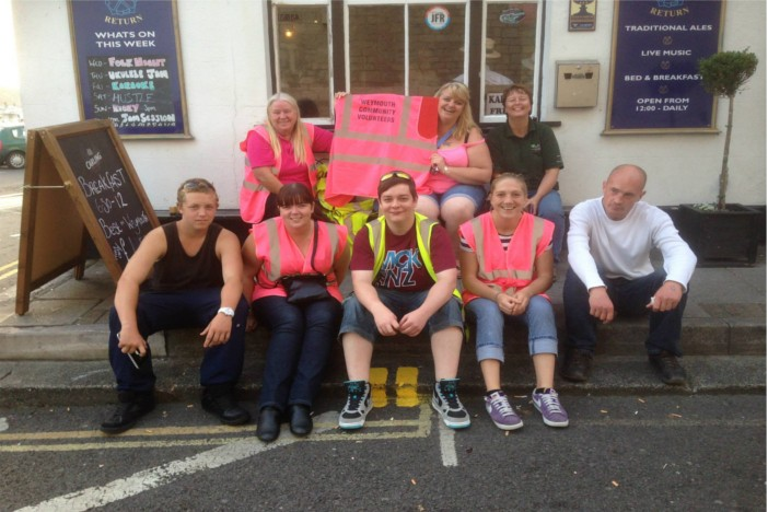 Weymouth Community Volunteers sat on pavement in Weymouth