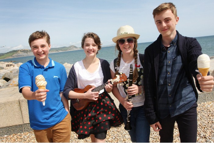 Young people with ice cream and guitar on the beach in Weymouth